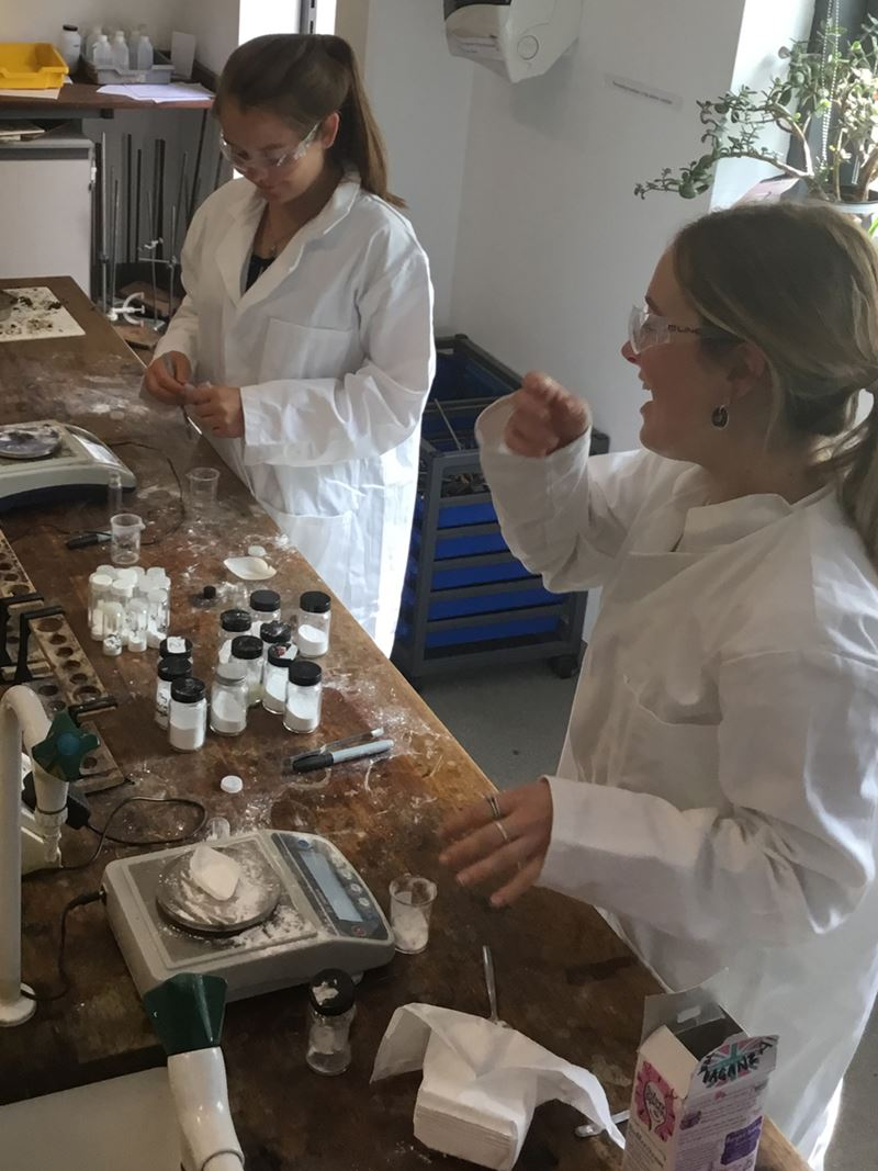 Two girls in lab coats and safety specs laughing and smiling at each other while weighing out a white powder onto weighing scales