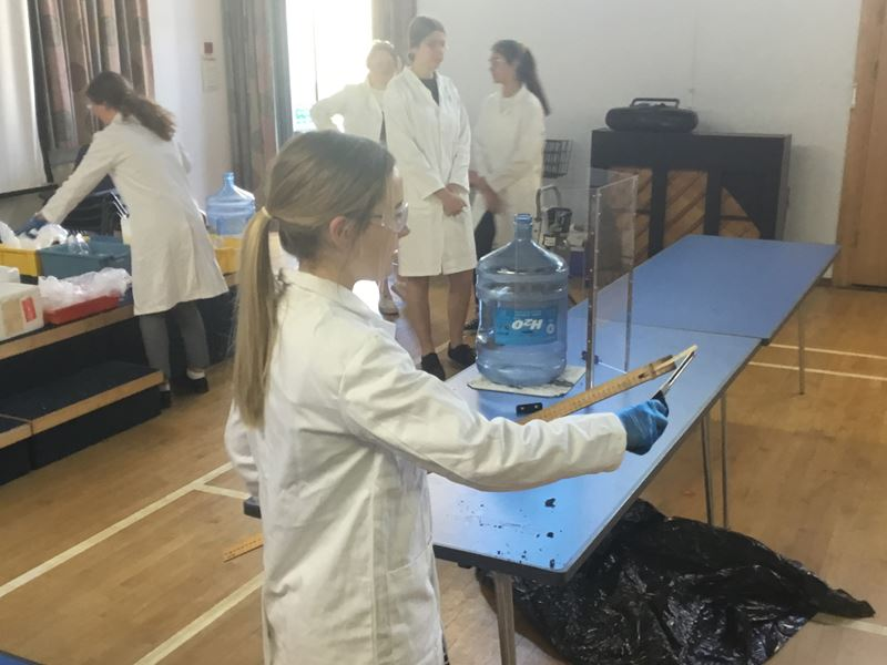 Girl in lab coat and safety specs uses a lighter to set light to a wooden taper taped to the end of a long ruler
