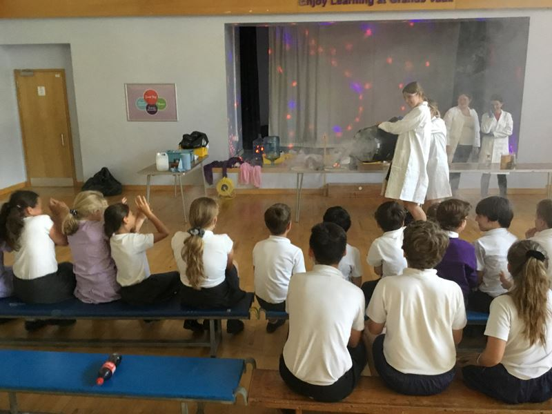 Primary school children in uniform sit on benches watching older girls in safety equipment pour liquid nitrogen out of a large container with clouds of water vapour