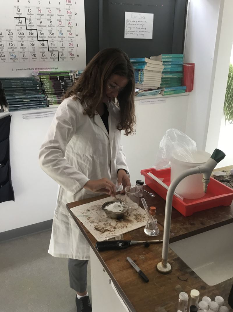 Girl in lab coat and safety specs stirs some white powder in a bowl on a laboratory bench
