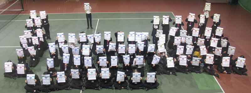 118 schoolchildren, photographed from above, are arranged in the shape of the periodic table. Each is holding up a large printout of one of the elements from the Compound Interest infographic periodic table.