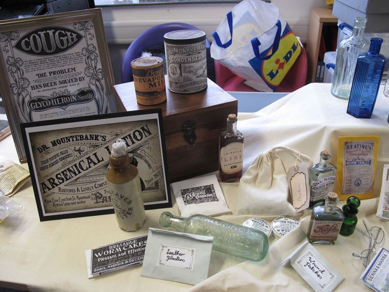 """An arrangement of historical medicine bottles and boxes, with title's such as """"Dr Mountebank's Arsenical Lotion"""" and """"Reliable Worm Cake – Pleasant and Effective"""""""