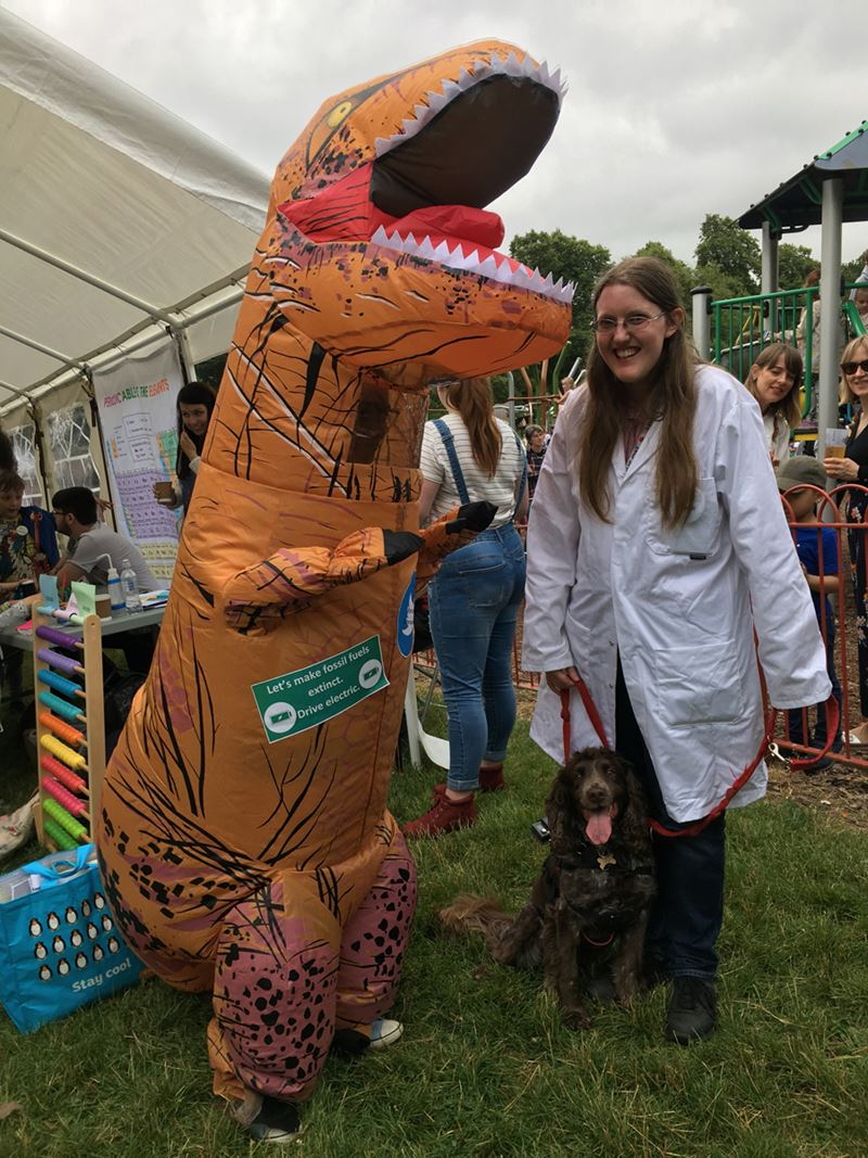 "A woman in a lab coat, holding onto a dog on a lead, poses next to a person wearing an inflatable dinosaur costume. The costume has a label on it saying ""Let's make fossil fuels extinct. Drive electric."""