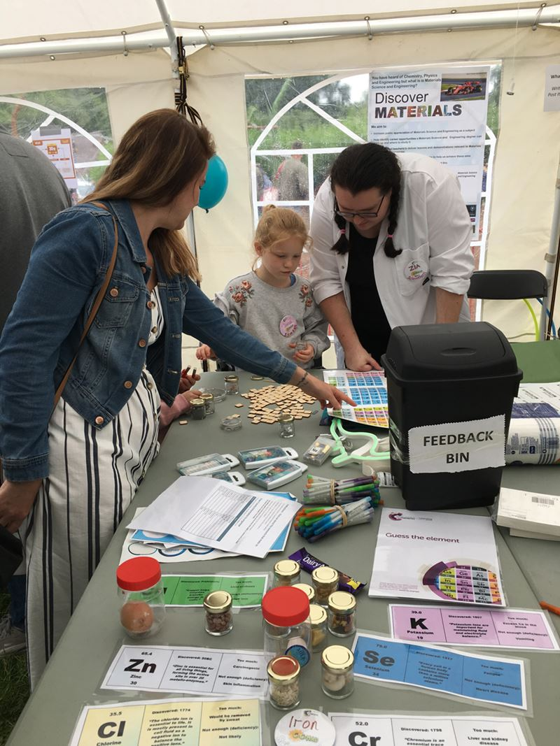 A parent, a child, and a volunteer in a labcoat pore over a table holding various chemistry activities, including a large periodic table, jars with various substances in them, and information cards about different elements.