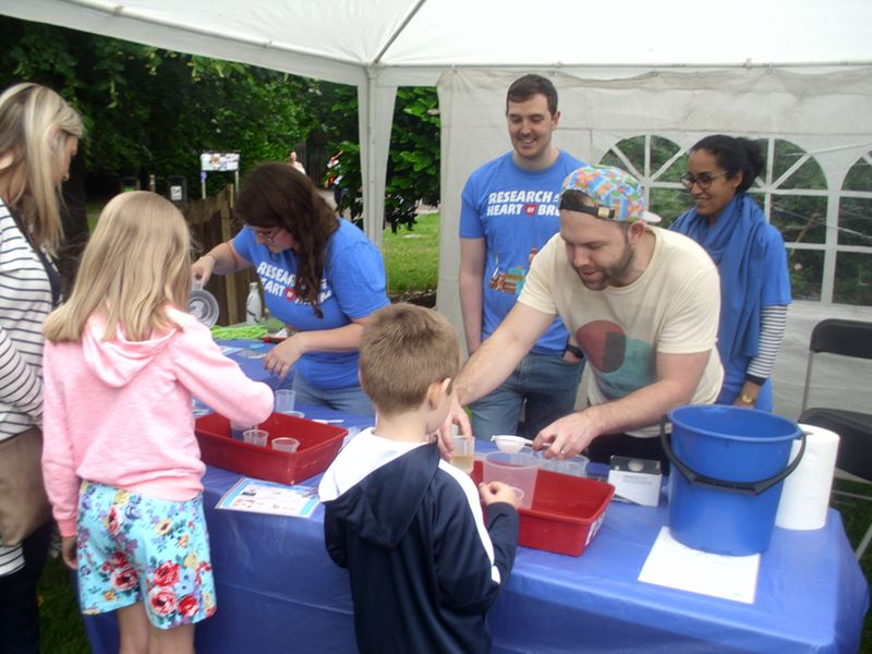 Volunteers doing experiments with children in a marquee. The experiments involve beakers, liquids and tea strainers.