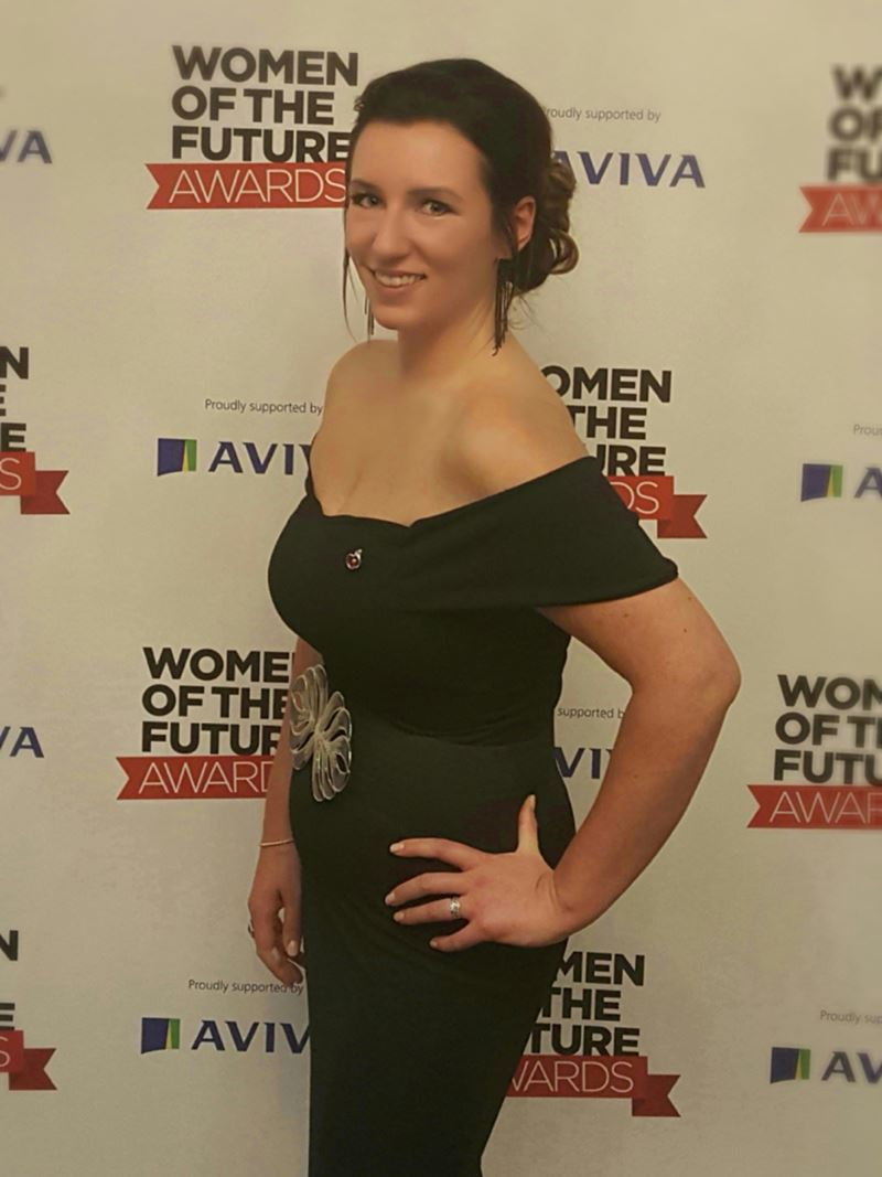 "Rebecca posing in an evening dress in front of a backdrop saying ""Women of the Future Awards"""
