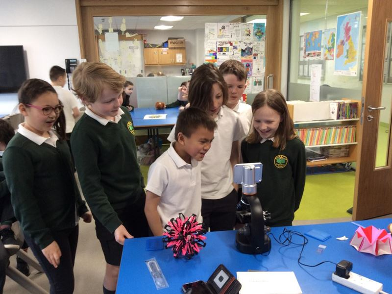 A small group of schoolchildren surround a microscope that has a screen display.