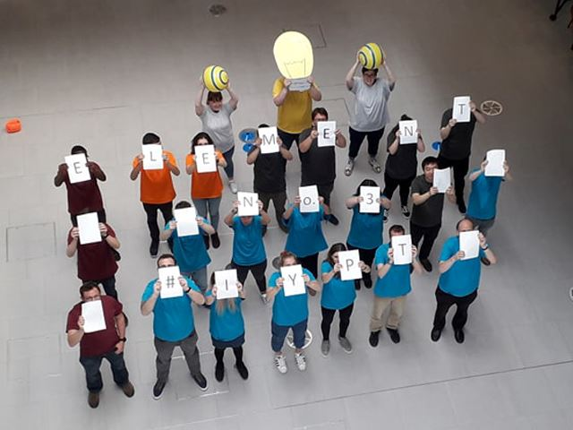 group of people holding up a sign each with one letter spelling element
