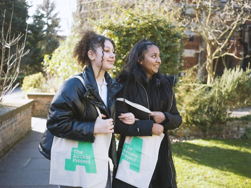 Two young female students in the grounds of an Oxbridge college, holding The Access Project bags and smiling and looking around them.