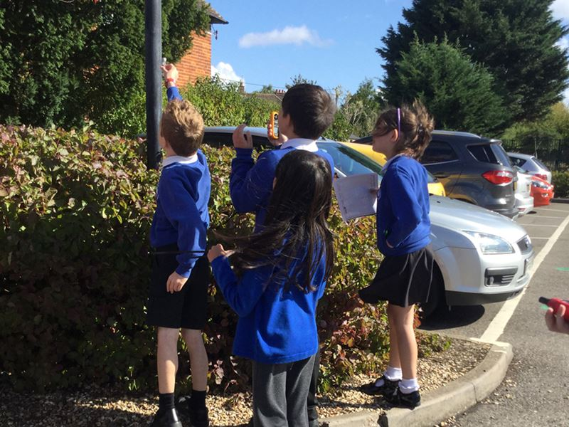 Schoolchildren in uniform, outside, holding up a small device to check air quality.