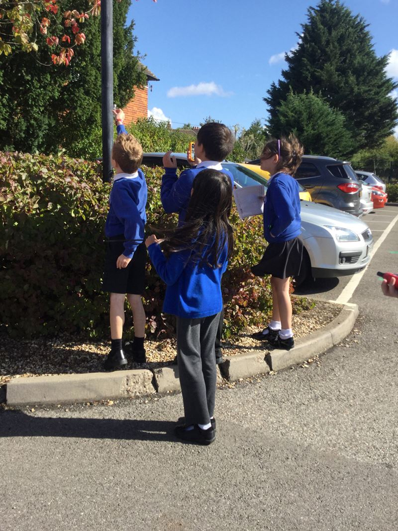 Primary school children in uniform standing outdoors and holding up a device to test the air.