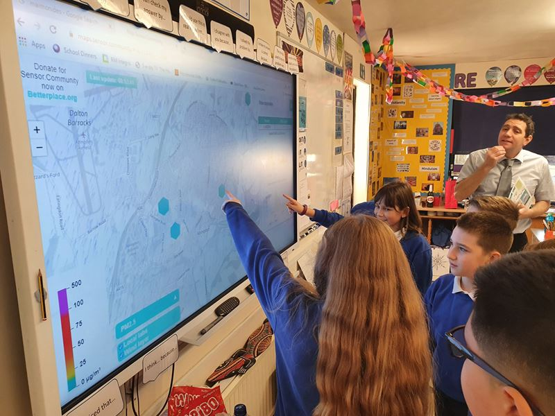 School children, supervised by a teacher, point to locations on a projected map.