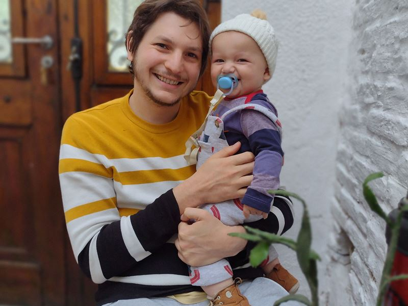 Researcher Julian Gargulio is pictured holding his smiling baby