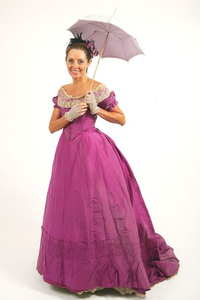 Carol Vorderman wearing a mid-Victorian dress in mauve