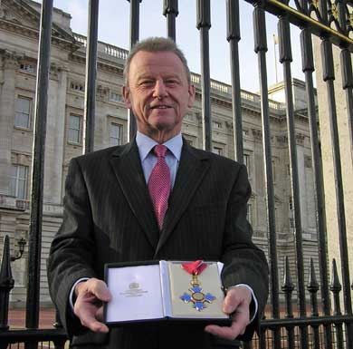 Dr Simon Campbell with his CBE outside Buckingham Palace