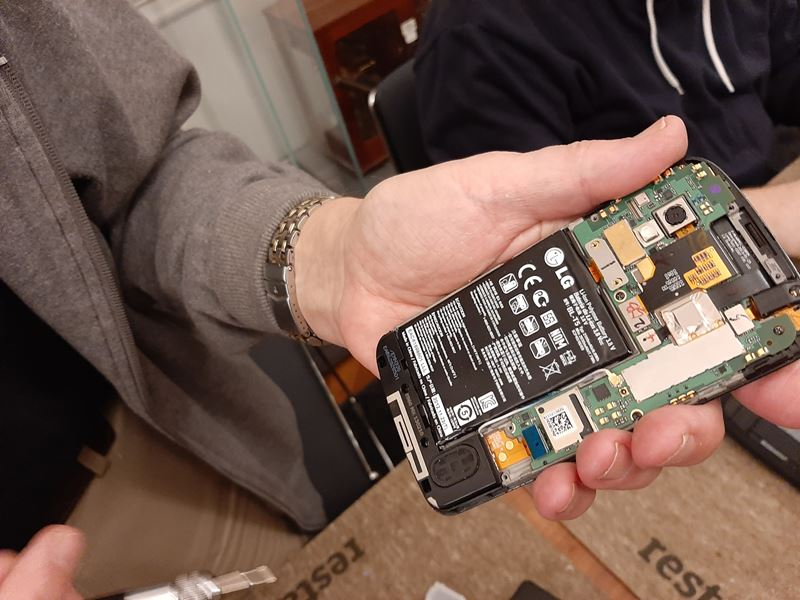 A mobile phone with its back removed to expose the electronic components. A hand is visible, pointing at key parts with a pen.