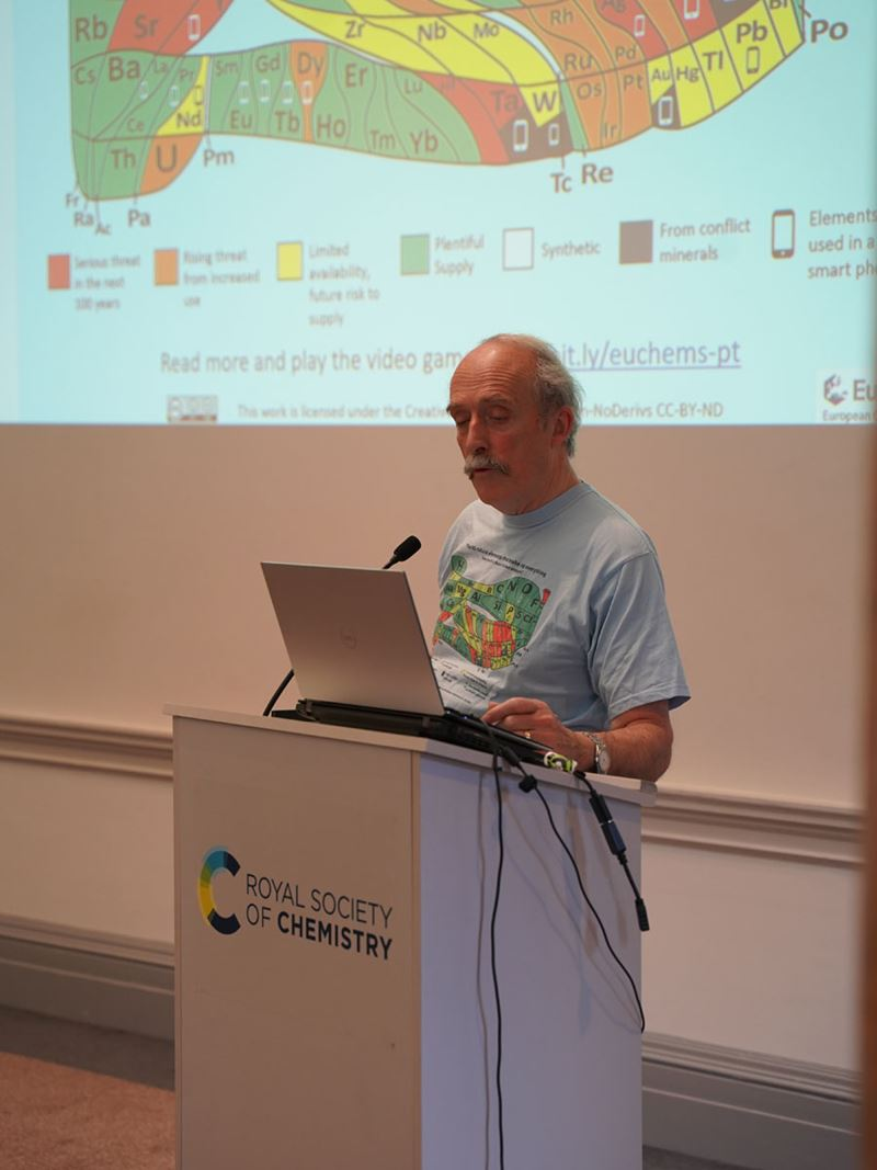 David Cole-Hamilton, wearing a T-shirt featuring the scarcity of the elements periodic table, speaks from behind a lectern. The scarcity of the elements periodic table is visible on a screen behind him.