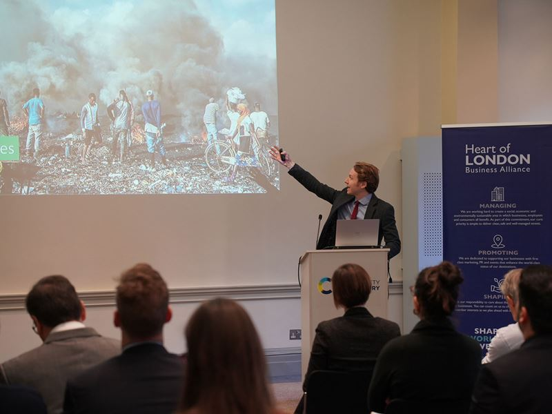 Ed Hubbard, speaking from behind a lectern, points at an image on the screen featuring a group of African men burning electronic equipment to extract the metals, with clouds of thick black smoke surrounding them