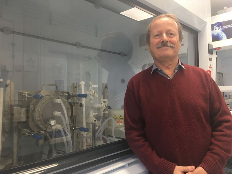 Professor Canham stands in front of a fume hood smiling at the camera