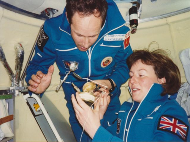Two astronauts in a confined space and zero gravity - opening a can of food with a couple of spoons floating nearby.