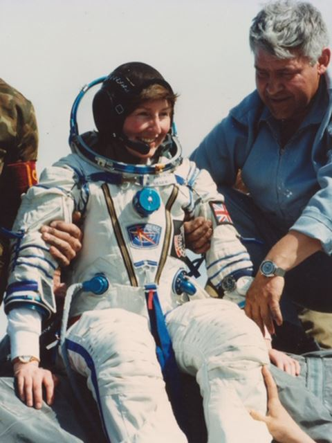 Helen in a spacesuit, smiling, while people support her from all sides.