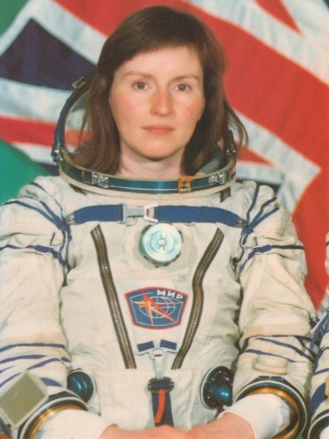 Helen Sharman sitting in front of a UK flag wearing a space suit.